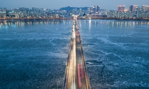Traffic passing over a bridge above the frozen Han River, before the Seoul city skyline.