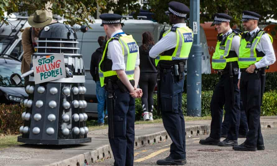 Met officers observe a Dalek bearing a sign saying 'Stop Killing People' at a protest against DSEI.