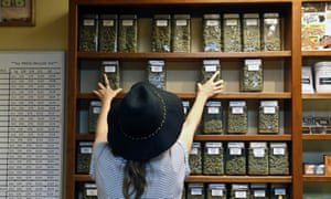 An employee arranges glass display containers of marijuana on shelves at a retail and medical cannabis dispensary in Boulder, Colorado on 11 August 2016.
