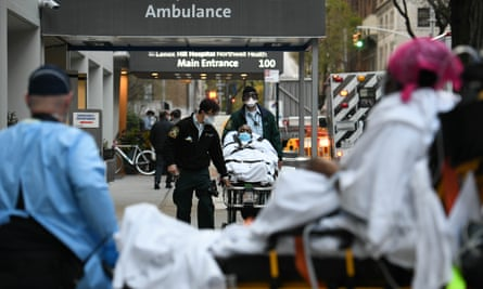 A man is wheeled out of Lenox Hill hospital in Manhattan as a woman, foreground, is wheeled into the emergency room on Friday, as the daily death toll from the coronavirus outbreak in the city neared 800 for the third straight day.