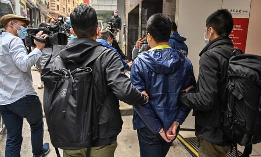 Police lead away one of the 55 people arrested on Wednesday