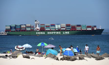 Beachgoers at Yarra Bay frolic while a Chinese container ship comes in to berth in Sydney