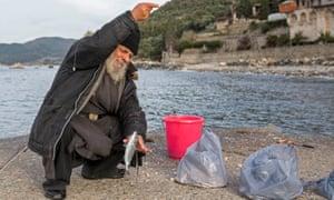 Ένας μοναχός ψαρεύει έξω από το μοναστήρι του Ξενοφώντος.