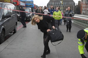 A woman ducks under a police tape after an incident on Westminster Bridge as people are moved away