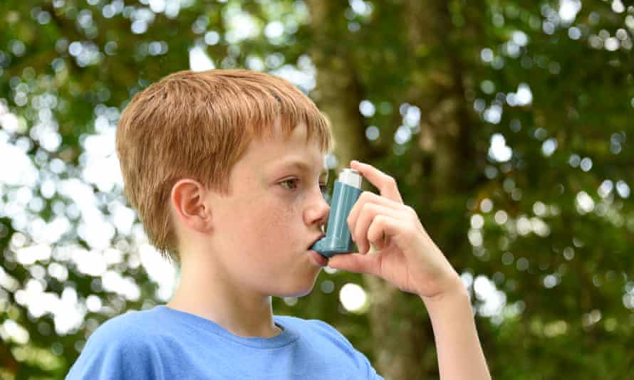 Boy using an asthma inhaler outdoors.