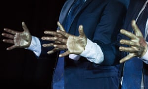 A close-up detail of two men in suits' hand gestures.