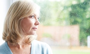 Posed by model Sad Mature Woman Suffering From Agoraphobia Looking Out Of Window