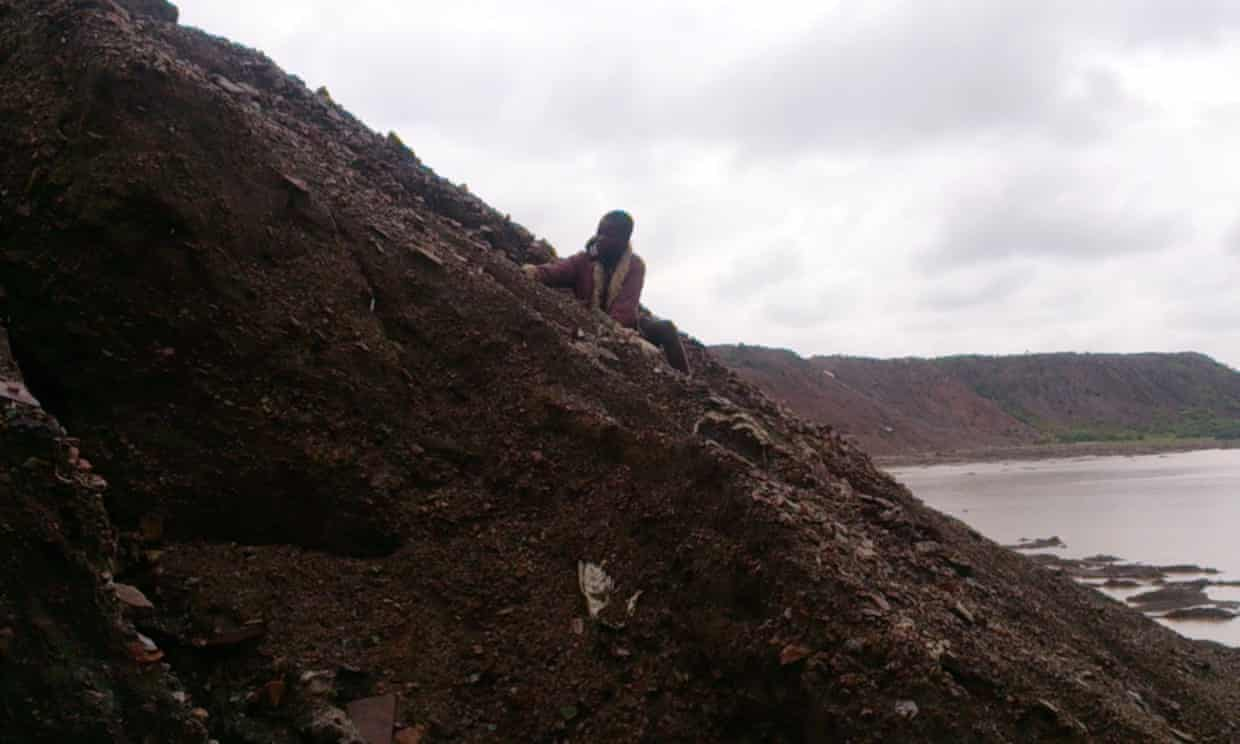 Child digging for cobalt on the industrial mine hill adjacent to Lake Malo in Democratic Republic of Congo.