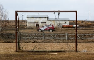 A car is seen through a goalpost while driving along a road in the Siberian village of Tyulkovo, Krasnoyarsk region, Russia
