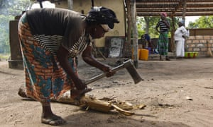 Zeneba Simon chops kindling for the kilns at the bakery in Bamingui, Central African Republic, as Yvette Akaba (in white) and Estella Yarsara look on.
