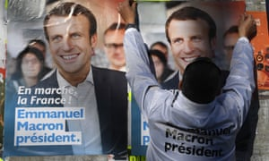 A supporter of French presidential election candidate for the En Marche ! movement, Emmanuel Macron, puts up electoral posters i