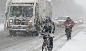 Cyclists ride through traffic in the snow during a late season snowstorm in New York City on Tuesday.