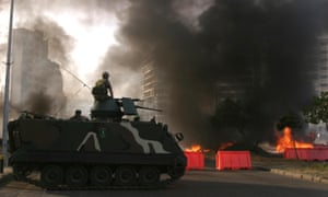 A Lebanese soldier sits on his armoured vehicle near burning tires in May 2008. Supporters of Lebanon's Hezbollah-led opposition blocked roads with burning tires and paralyzed the airport in the capital Beirut to enforce a strike against the Western-backed government.
