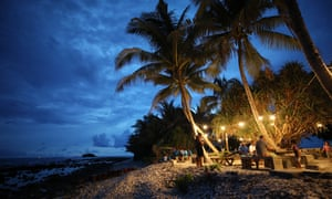 People gather at an outdoor cafe next to the Pacific Ocean at dusk in Funafuti, Tuvalu, which like many Pacific nations has had no confirmed cases of coronavirus.