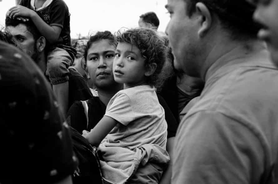 Young Chelita clings to her mother amid the chaos of migrants waiting to be admitted into Mexico
