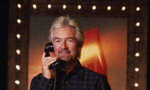 Noel Edmonds in his role as host on Deal or No Deal holding a telephone.