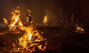 People cremate the bodies of at a crematorium ground in New Delhi, yesterday