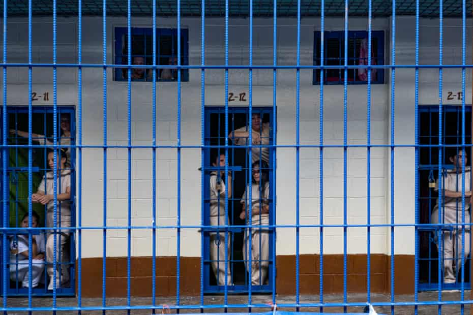 Inmates stand at the doors to their cells at the Ilopango women's prison