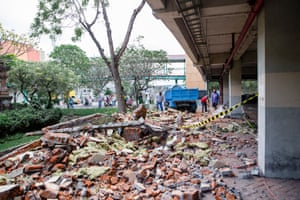 Workers cleanup parts of a shopping mall building which collapsed after an earthquake, in Denpasar, Bali.
