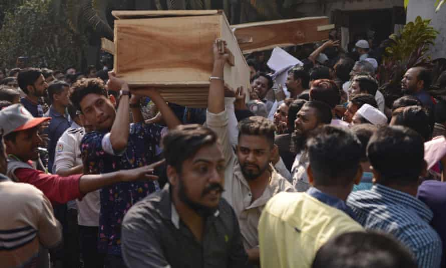 Bangladeshis carry coffins of relatives out from a morgue after the fire in Dhaka.