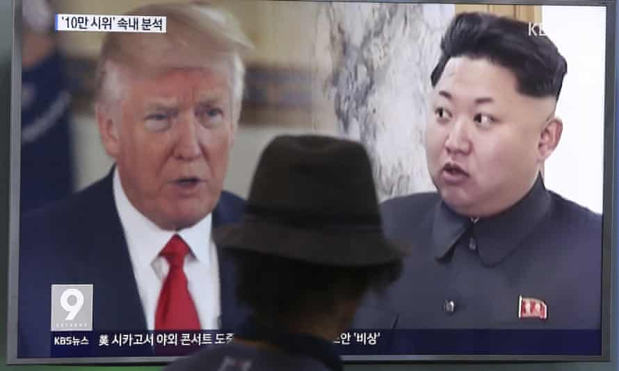 A man watches a television screen showing President Donald Trump and North Korean leader Kim Jong-un during a news programme at a train station in Seoul, South Korea