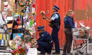 Police place tributes on a memorial wall as police lines are relaxed around the Linwood Mosque in Christchurch.