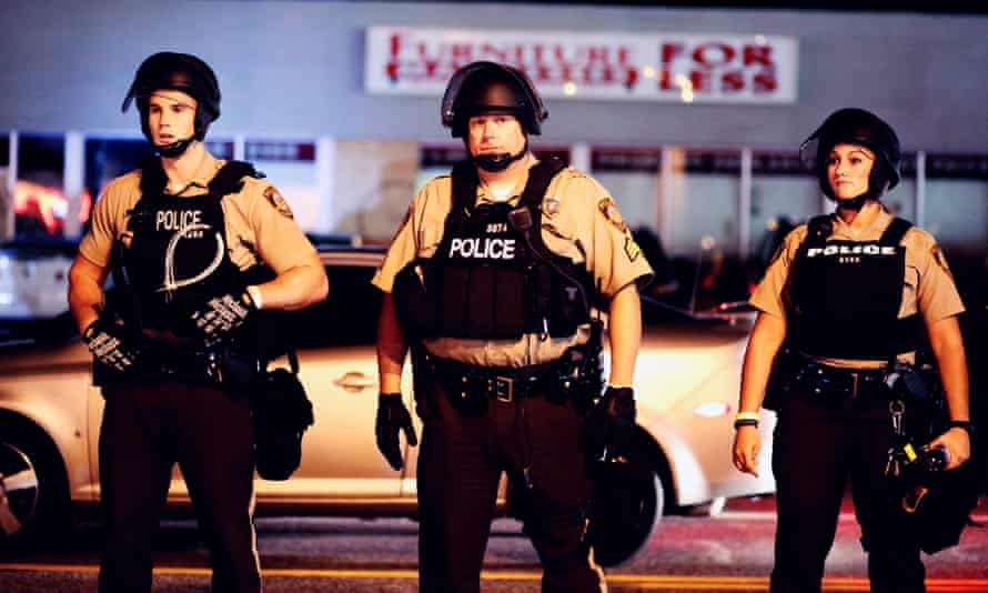 Police stand guard during a protest in Ferguson on the anniversary of the shooting of unarmed 18-year-old Michael Brown
