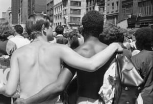 Back view of pair of shirtless men as they walk, arm in arm, during the first Stonewall anniversary march, then known as Gay Liberation Day (and later Gay Pride Day), New York, New York, June 28, 1970.