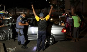 Police officers search people on New Year's Eve in Johannesburg, South Africa. Police have been more stringent in enforcing restrictions since a partial lockdown was reinstated last month.