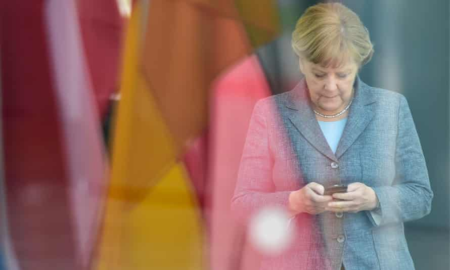 Angela Merkel looks at her smartphone at the chancellery in Berlin.