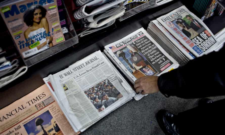 A customer picks up a copy of a newspaper at a newsstand in New York, US.