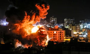 Fire and smoke billow above buildings in Gaza City during Israeli strikes.