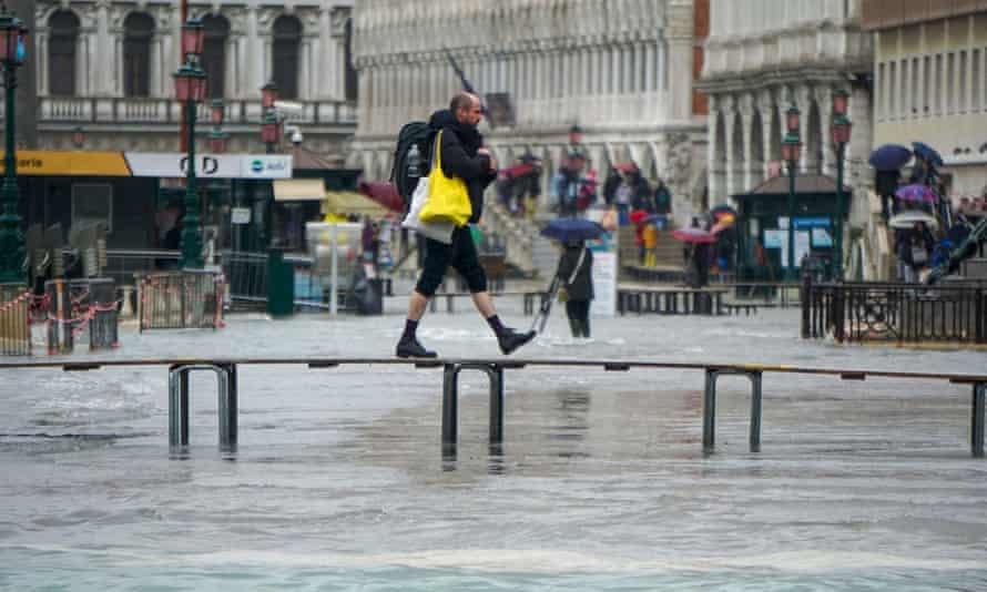 A man walks across an improvised bridge over a flooded Venice street