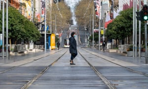 A woman crosses the tram tracks on a quiet Bourke Street during Melbourne's lockdown.