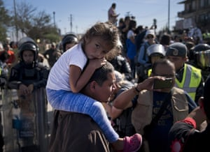A young migrant sits on a man's shoulders as they join a group of migrants trying to push their way past the Chaparral border crossing in Tijuana, Mexico, Sunday, Nov. 25, 2018. The mayor of Tijuana has declared a humanitarian crisis in his border city and says that he has asked the United Nations for aid to deal with the approximately 5,000 Central American migrants who have arrived in the city. (AP Photo/Ramon Espinosa)