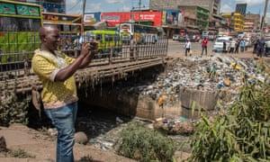 Environmental activist takes a photo of garbage in Nairobi river