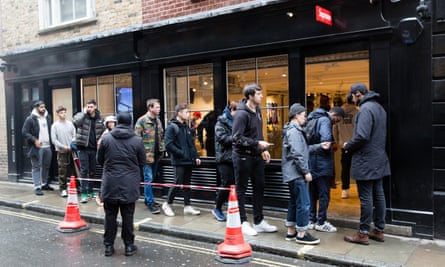 Customers hand over their tickets to gain access to the Supreme Soho store.