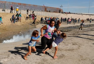 A migrant family, part of a caravan of thousands traveling from Central America to the United States, run away from teargas canisters fired by US border patrol officers in front of the wall between the US and Mexico.