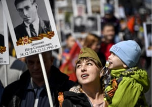 Participants in Vladivostok hold portraits of relatives who fought in the second world war