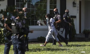 A protester is arrested on 15 July after sitting in the front yard of the home of the Kentucky attorney general, Daniel Cameron, in Louisville, Kentucky, chanting Breonna Taylor's name as well as calling for justice.