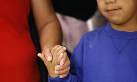 A mother and son from Guatemala hold hands during a news conference on 9 July following their reunion in Linthicum, Maryland, after being reunited following their separation at the US border.