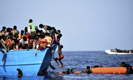 Migrants wait to be rescued as they drift in the Mediterranean, some 12 miles north of Libya.