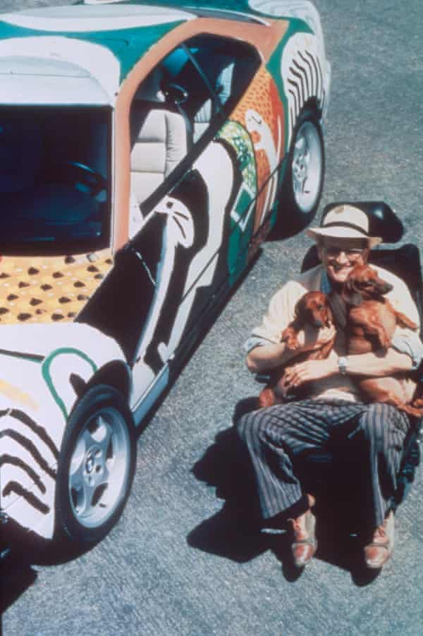 Artist David Hockney sits in a chair with his sausage dogs beside a painted car