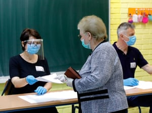 Election officials check voters' ID cards during the Croatian parliamentary election