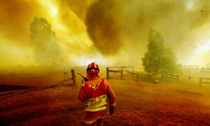 A fireman watches as a bushfire comes up a gully and over a house at Gibbo Park, Victoria on 22 January, 2003.