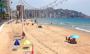 View of a sunny, empty beach with social distancing markers and Benidorm's high-rises in the background.