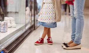 Little girl strolling at shop window with mother