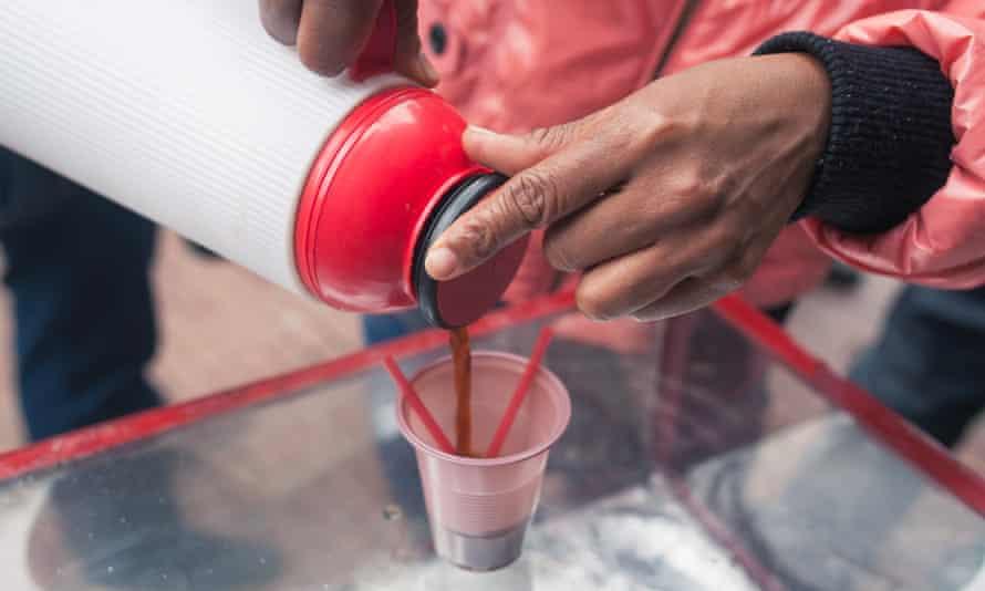 A street vendor pouring a cup of tinto.