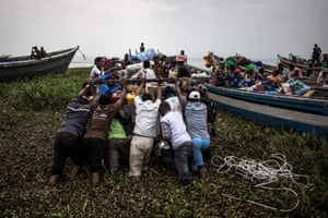 Internally displaced people push out a boat in Tchomia