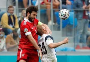 Russia's Georgi Dzhikiya beats Finland's Joel Pohjanpalo in the air.